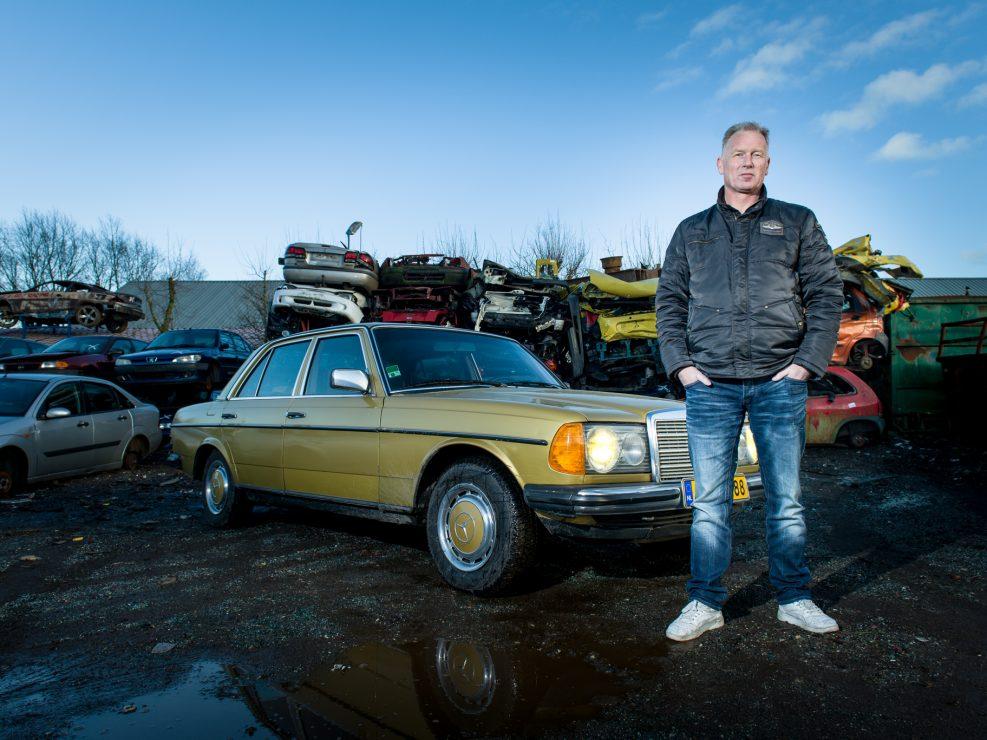 """Jan Menno Zijlstra naast zijn Mercedes-Benz 250 uit 1977. """"Mijn Mercedes is mooi van lelijkheid, het heeft ook wel een aparte kleur. Opa noemde zijn auto altijd 'De Gouden Koets', niemand anders mocht in zijn Mercedes rijden. Toen opa kwam te overlijden wilde mijn familie de auto verkopen, maar daar heb ik een stokje voor gestoken. De trots van opa verkopen we niet."""" Jan Menno Zijlstra (49 jaar) is agrarisch adviseur buitendienst bij Univé Dichtbij. Dat hij terechtgekomen is in 'het agrarische' is geen wonder. """"Mijn opa was boer, veekoopman en een goede ondernemer. Hij was een echte autoliefhebber en reed graag in grote, mooie auto's."""" Als je goed boert mag je dat ook een beetje laten zien en Jan Menno zijn opa was trots op zijn auto: """"Behalve zijn familie was zijn auto zijn alles. Iedere zaterdag werd ze gewassen, gepoetst en onderhouden."""" Zelf vindt Jan Menno de ster op de motorkap en het grote stuurwiel heel mooi. Het interieur is typerend voor de tijd; bruin pluizige bekleding, bruine kunststof aan de binnenkant van de portieren en bruin waar je ook kijkt. """"Als je er in zit kom je erachter hoe lekker de stoelen zitten. De auto ruikt ook nog helemaal naar mijn opa. Die lucht krijg je er ook niet meer uit, maar dat hoeft ook helemaal niet van mij."""" Tot het allerlaatste moment hield Jan Menno's opa zich nog bezig met zijn auto. """"Op zijn sterfbed zei opa; 'kom, we gaan nog even een rondje rijden in de Mercedes.' Dit kon hij toen natuurlijk niet meer, maar dat zei hij vroeger vaak tegen mij als we er op uit gingen voor een ritje."""" EEN GROEIENDE SERIE INDRINGENDE PORTRETTEN VAN MENS & AUTOMOBIEL Deze serie"""